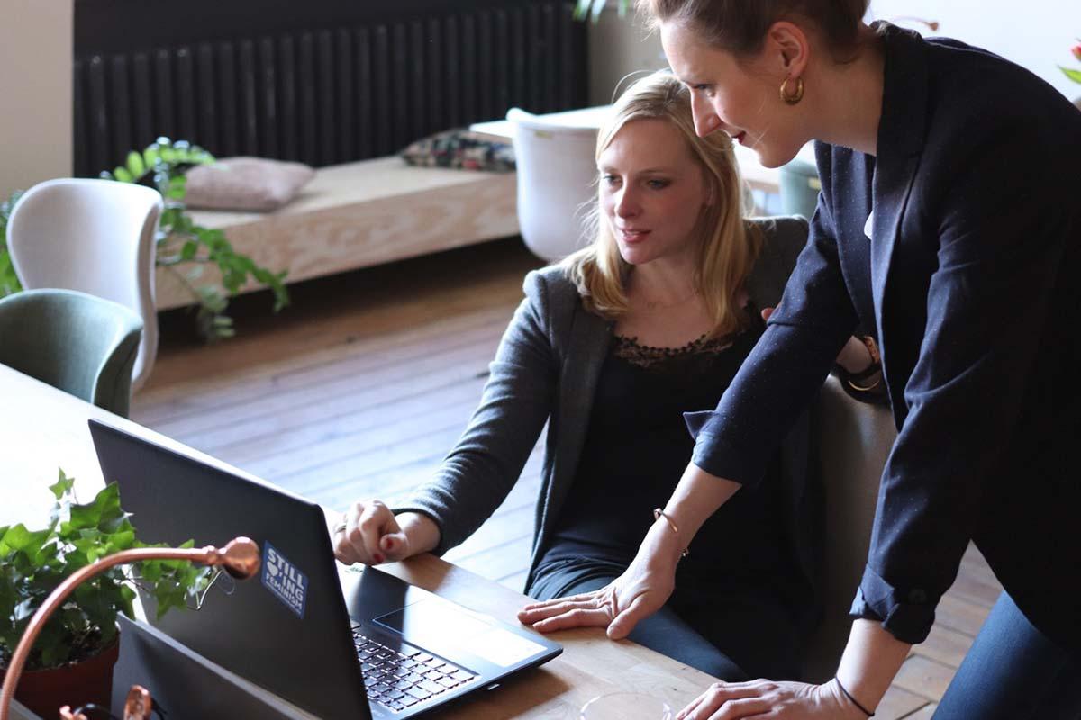 wo-women-using-on-black-laptop-computer